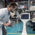 employé d'une entreprise industrielle devant une borne numérique