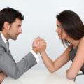 une femme et un homme face à face faisant un bras de fer