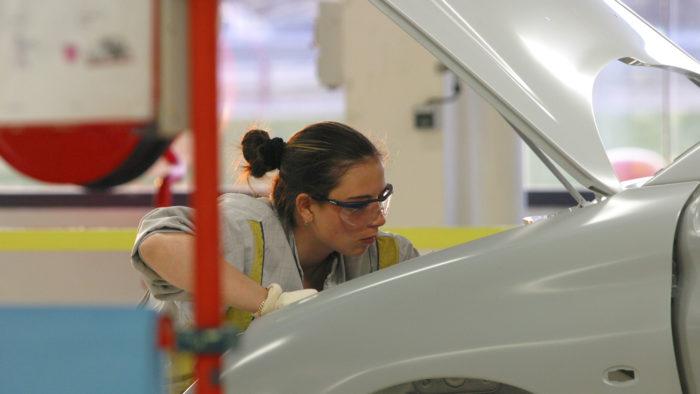 gros plan sur une jeune fille travaillant sur la carrosserie d'une voiture