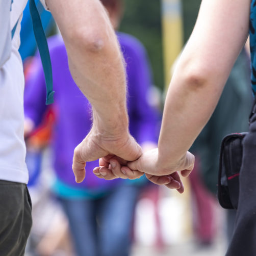 gros plan sur deux mains se tenant par les petits doigts (danse bretonne)
