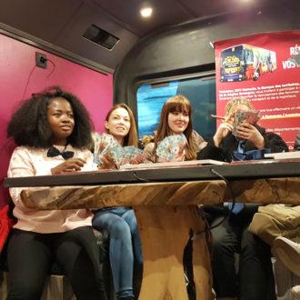jeunes filles jouant autour d'un table dans le bus escape game de Transdev