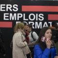 """public mélangé d'hommes-femmes, vieux-jeunes passant devant une accroche """"métiers emplois formations"""""""