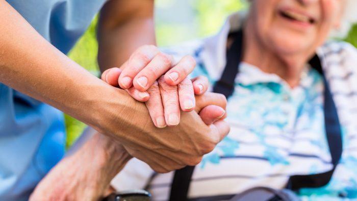 Gros plan sur les mans d'une aide soignante et d'une dame âgée
