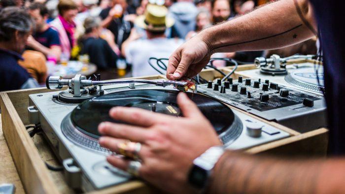 gros plan sur un DJ mettant un disque vinyle sur une platine