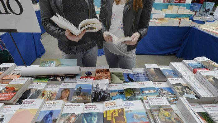 Jeunes filles lisant devant un étal de livres