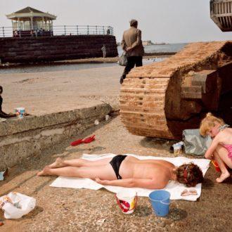 Gros plan sur deux enfants anglais jouant comme à la plage à l'ombre d'un tank abandonné dans une fiche industrielle près de la plage
