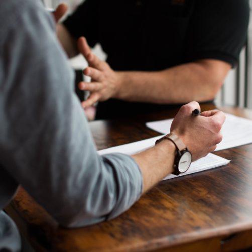 Vue sur une table et les mains de 2 hommes en réunion de travail