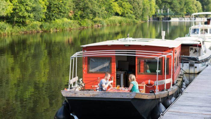 Touristes prenant leur petit déjeuner à bord d'une péniche à quai, sur le Blavet à Vue sur le Blavet, à Bieuzy-les-Eaux (56)