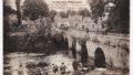 Photo ancienne en noir et blanc - Vue animée du Blavet et du pont de pierre. Au premier plan, des femmes lavent leur linge au bord de la rivière. 1923