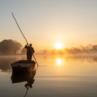 Pêcheur sur une barque dans les marais de Glénac (56) au lever du jour