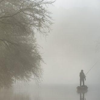 Pêcheur sur le canal à bord d'une barque dans la brume