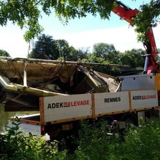 Une épave de voilier chargée sur un camion s'apprête à rejoindre une usine de recyclage