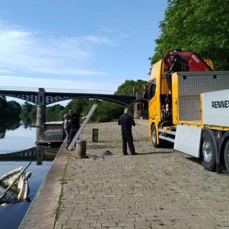 Les agents de la Région s'apprêtent à extraire un petit voilier coulé dans la Vilaine, près du quai sur la commune de Langon