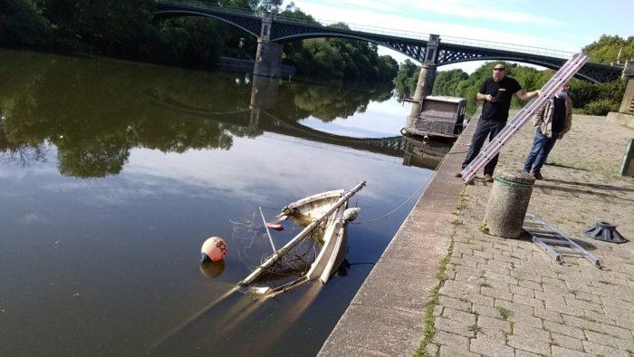 Les agents de la Région s'apprêtent à extraire un petit voilier coulé dans la Vilaine